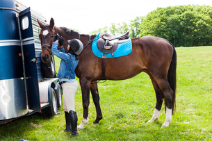 Horse rider putting on horse's bridleの写真素材 [FYI03516460]