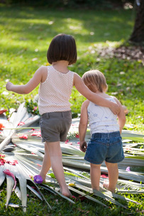Girl with arm around toddler sister with flower and leaf display in gardenの写真素材 [FYI03516499]