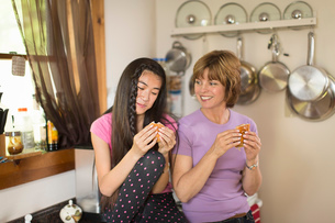 Mid adult woman and teenage girl in kitchen, eating snackの写真素材 [FYI03516516]