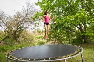 Teenage girl jumping on trampoline, outdoorsの写真素材 [FYI03516525]