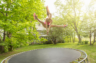 Teenage girl jumping on trampoline, outdoorsの写真素材 [FYI03516696]
