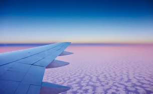 Atmospheric elevated view of airplane wing above the cloudsの写真素材 [FYI03516736]