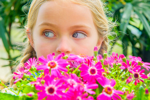 Close up portrait of girl looking sideways behind pink flowersの写真素材 [FYI03516816]