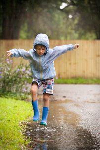 Boy in rubber boots jumping in rain puddleの写真素材 [FYI03516951]