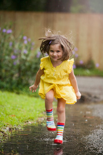 Girl wearing rubber boots running in rain puddleの写真素材 [FYI03516953]