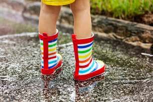 Legs of girl wearing rubber boots standing in rain puddleの写真素材 [FYI03516956]