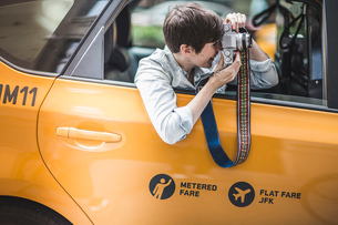 Woman photographing from yellow taxi, New York, USの写真素材 [FYI03516990]