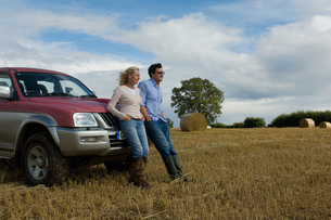 Mother and son leaning against four wheeled drive in harvested fieldの写真素材 [FYI03517208]