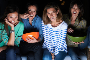 Four women laughing and watching TV with snack bowlsの写真素材 [FYI03517216]