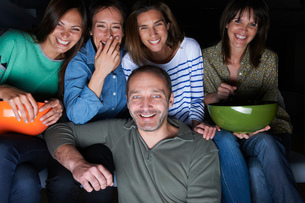 Five adult friends laughing and watching TV with snack bowlsの写真素材 [FYI03517217]