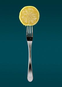 Still life of fresh slice of lemon on forkの写真素材 [FYI03517241]