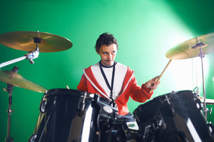 Male student playing drums in college music roomの写真素材 [FYI03517274]