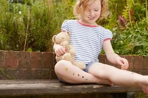 Girl sticking stars on legs on garden seatの写真素材 [FYI03517310]