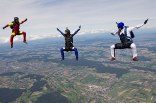 Team of three skydivers in sit fly position over Buttwil, Luzern, Switzerlandの写真素材 [FYI03517351]