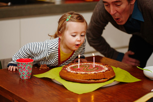 Young girl blowing out birthday candles on cakeの写真素材 [FYI03517354]