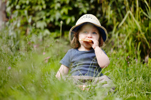 Young girl sitting in grass eating snackの写真素材 [FYI03517367]