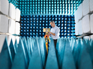 Male scientist preparing to measure electromagnetic waves in anechoic chamberの写真素材 [FYI03517445]