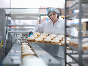 Female baker putting cakes on packaging line in cake factoryの写真素材 [FYI03517683]