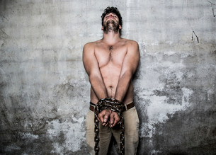 Bare chested young man with chains wrapped around his wristsの写真素材 [FYI03517718]