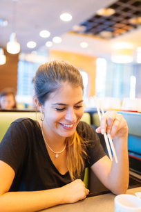 Young woman eating with chopsticks in restaurant, Manila, Philippinesの写真素材 [FYI03517812]