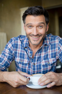 Portrait of handsome mature man drinking coffee in cafeの写真素材 [FYI03517850]