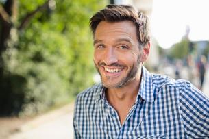 Portrait of handsome smiling mature man on streetの写真素材 [FYI03517863]
