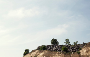 Abandoned quarry clifftop with rocks and bushesの写真素材 [FYI03517927]