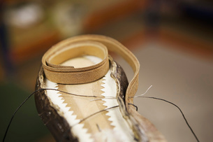 Close up of thread and shoe leather in shoe makers workshopの写真素材 [FYI03517972]