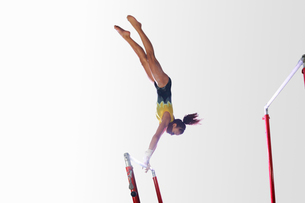 Young gymnast performing on uneven barsの写真素材 [FYI03518162]