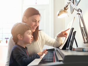 Mother pointing at sheet music to teach son to play piano at homeの写真素材 [FYI03518217]
