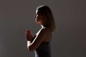 Silhouetted low key shot of young woman practicing yogaの写真素材 [FYI03518314]