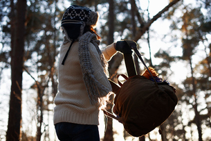 Mature female backpacker lifting up backpack in forestの写真素材 [FYI03518360]