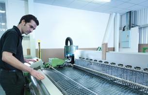 Worker operating carbon fibre loom in carbon fibre factoryの写真素材 [FYI03518525]