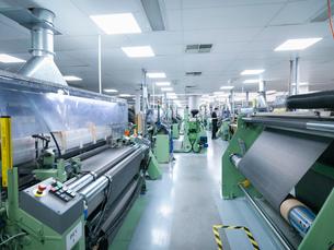 Worker operating carbon fibre loom in carbon fibre factoryの写真素材 [FYI03518528]