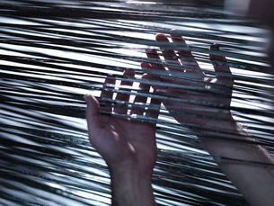 Close up of hands holding carbon fibre on loom in carbon fibre factoryの写真素材 [FYI03518530]