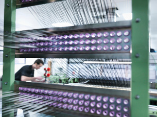 Worker weaving carbon fibre in carbon fibre factoryの写真素材 [FYI03518532]
