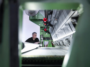 Worker inspecting carbon fibre on loom in carbon fibre factoryの写真素材 [FYI03518534]