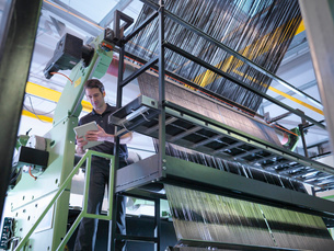 Worker inspecting carbon fibre on loom in carbon fibre factoryの写真素材 [FYI03518535]
