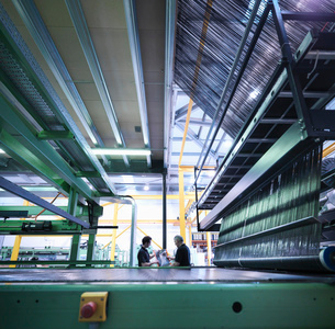 Worker inspecting carbon fibre on loom in carbon fibre factoryの写真素材 [FYI03518536]