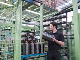 Worker carrying carbon fibre thread in carbon fibre factoryの写真素材 [FYI03518537]