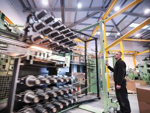 Worker operating carbon fibre loom in carbon fibre factoryの写真素材 [FYI03518539]