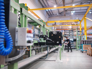 Worker operating carbon fibre loom in carbon fibre factoryの写真素材 [FYI03518540]
