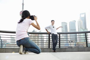 Male tourist posing for girlfriend with instant camera, The Bund, Shanghai, Chinaの写真素材 [FYI03518762]