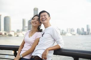 Tourist couple leaning against bridge railing looking up, The Bund, Shanghai, Chinaの写真素材 [FYI03518766]