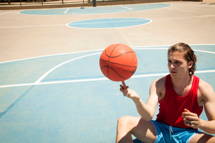Young male basketball player spinning ball on fingerの写真素材 [FYI03518819]