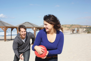 Young couple running with ball on beach, Tel Aviv, Israelの写真素材 [FYI03518963]
