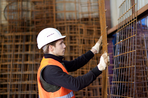 Factory worker moving wire mesh in concrete reinforcement factoryの写真素材 [FYI03518983]