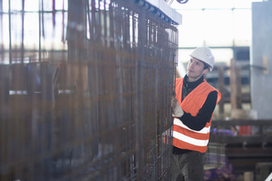 Young male factory worker choosing wire mesh in concrete reinforcement factoryの写真素材 [FYI03518990]