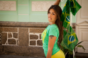 Young woman celebrating with Brazilian flags in the street, Rio de Janeiro, Brazilの写真素材 [FYI03519092]