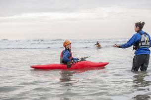 Female instructor helping young man in sea kayakの写真素材 [FYI03519309]